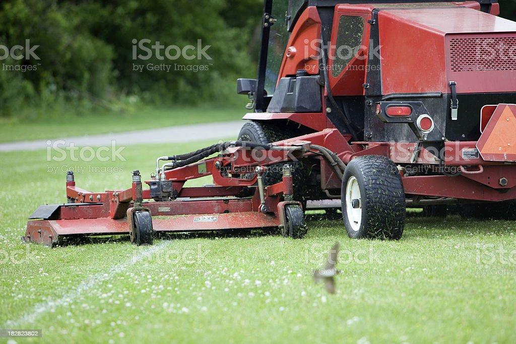 Commercial Lawn Mower Cutting Soccer Field Near Walking Path stock photo