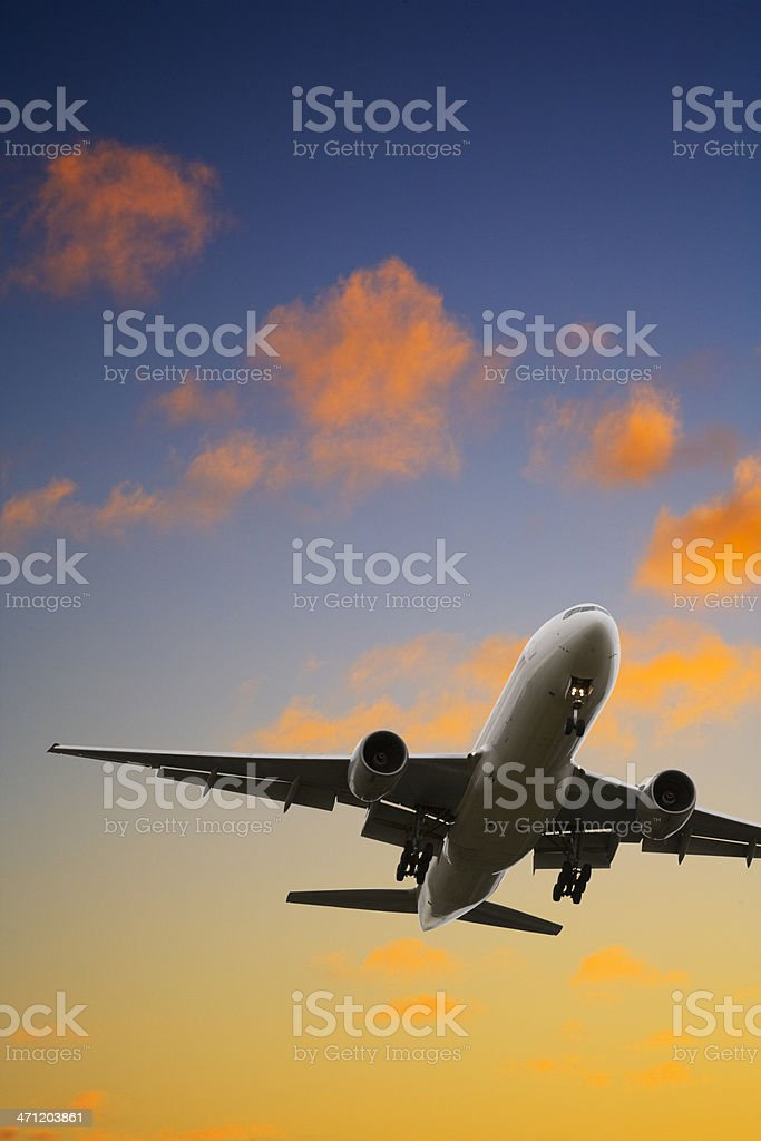 Commercial plane landing at dusk royalty-free stock photo