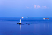 Commercial ship passing lighthouse