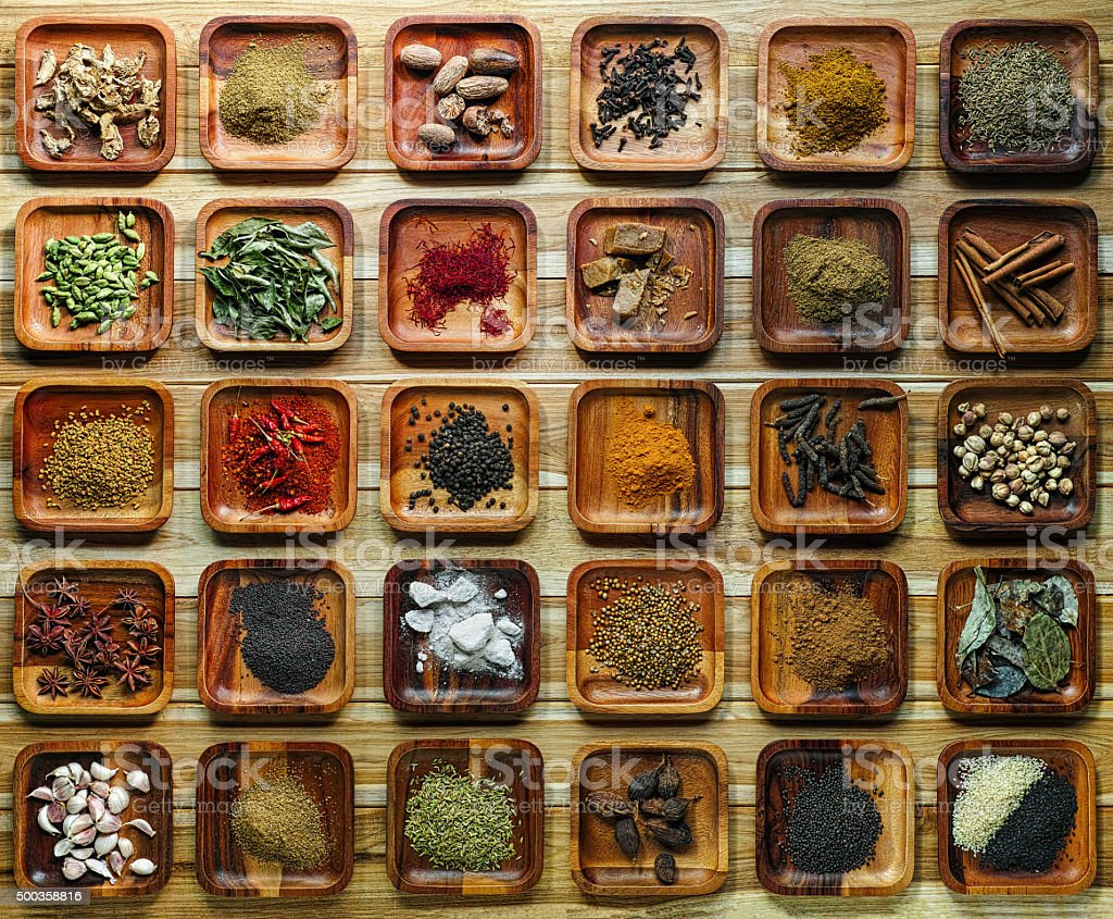 Common Indian herbs and spice ingriedients on wooden trays. stock photo
