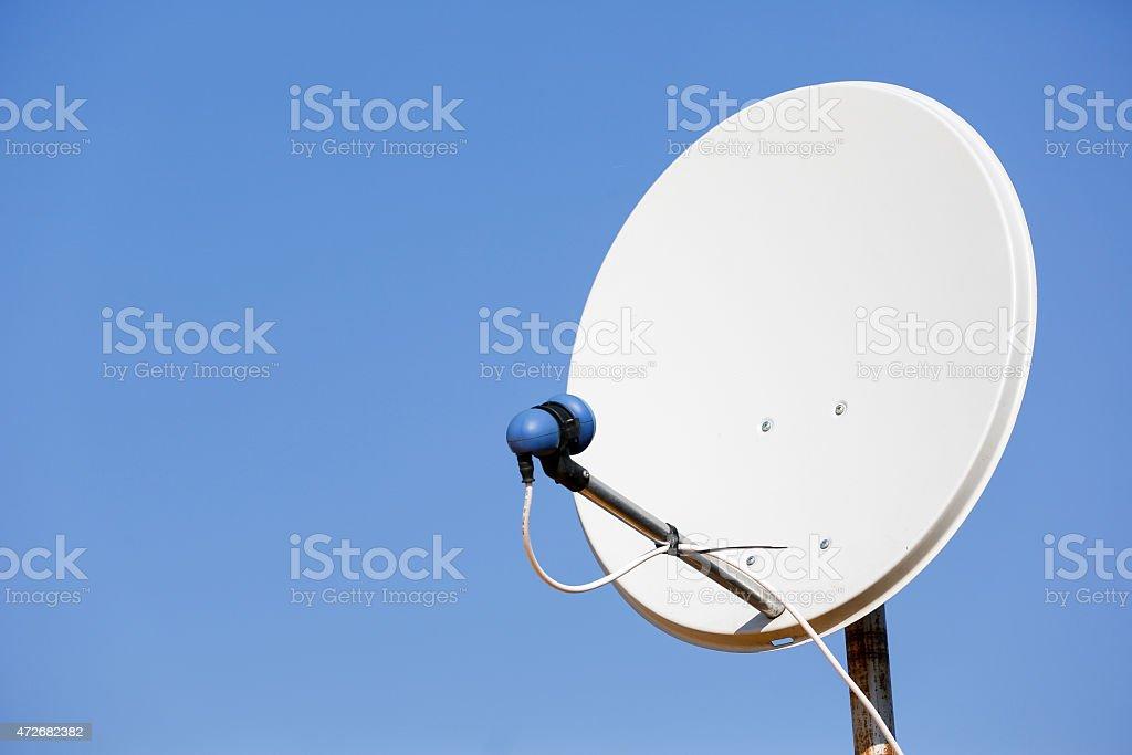 Common satellite dish against sky stock photo