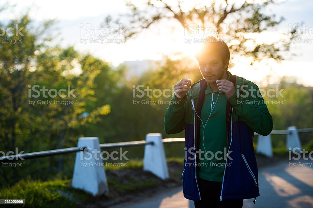 Common young man walking in the city listening to music stock photo