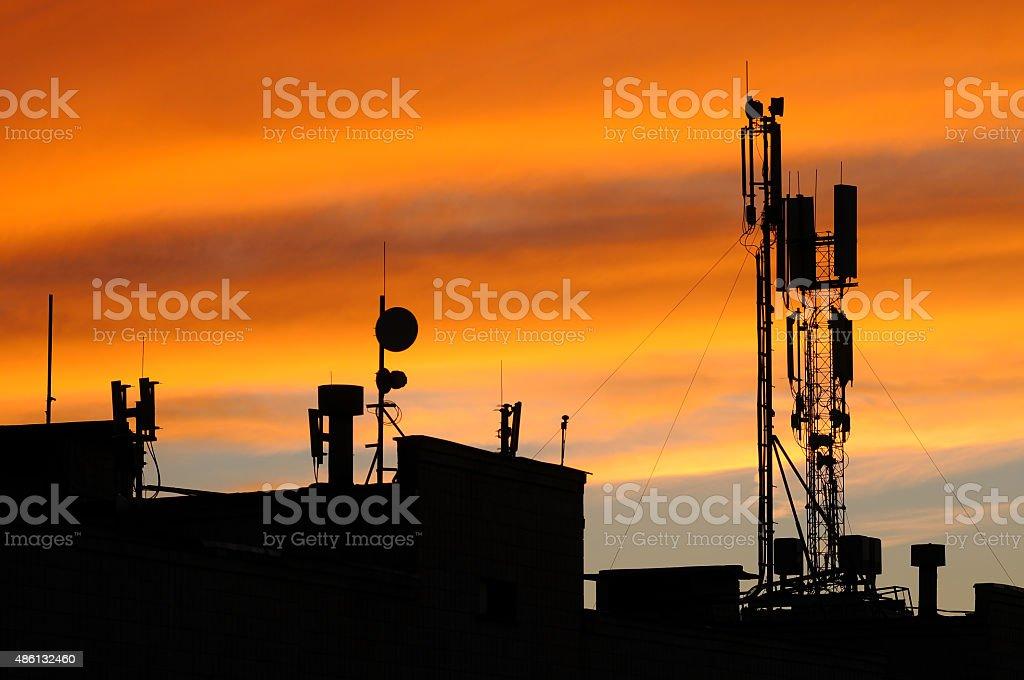 Communication antennas in an orange sunset stock photo