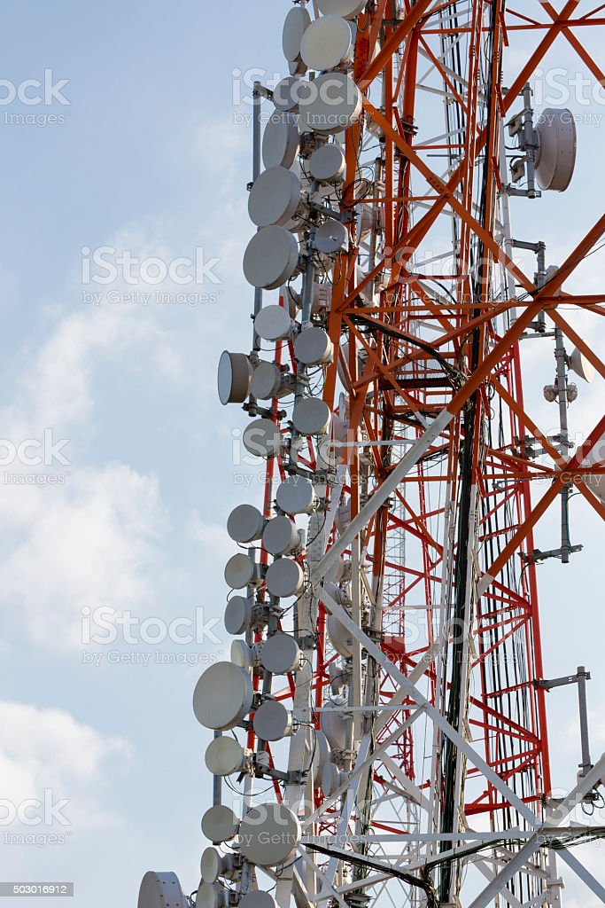 Communication tower and satellite dishes on blue sky background stock photo