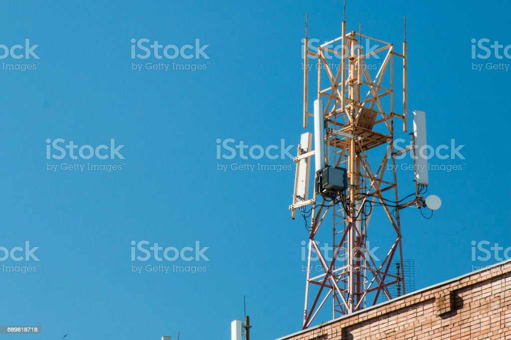 Communication tower on the roof of a building against the blue sky. stock photo