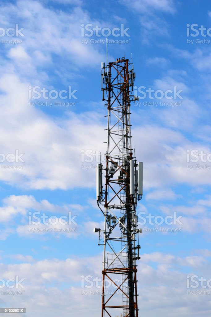 communication tower with mobile telephone antenna on cloudy sky background stock photo