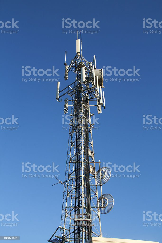 communications tower against blue sky stock photo