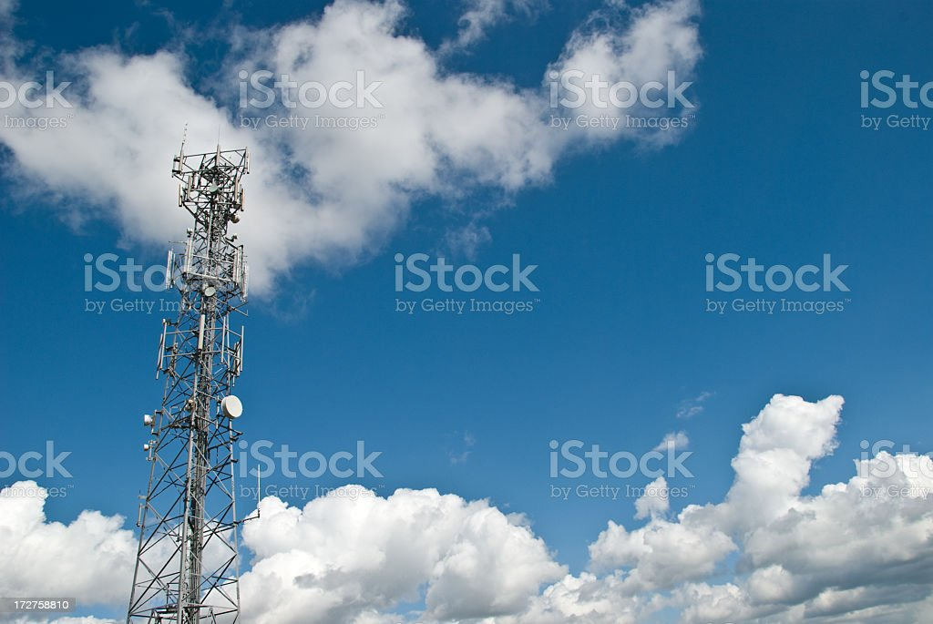Communications tower with cloudy sky background stock photo