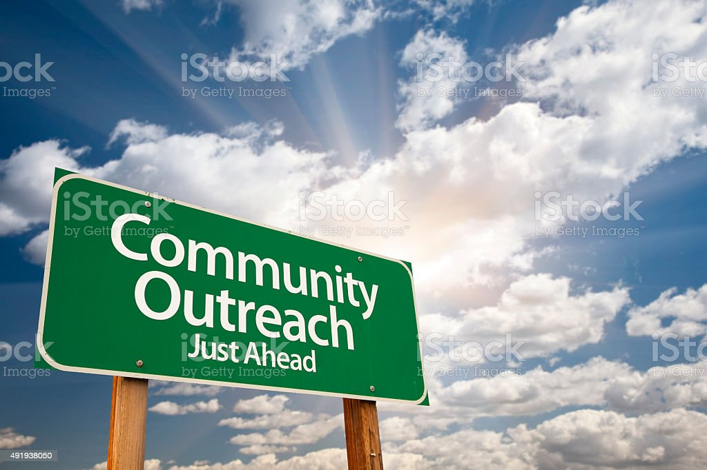 Community Outreach Green Road Sign Over Clouds stock photo