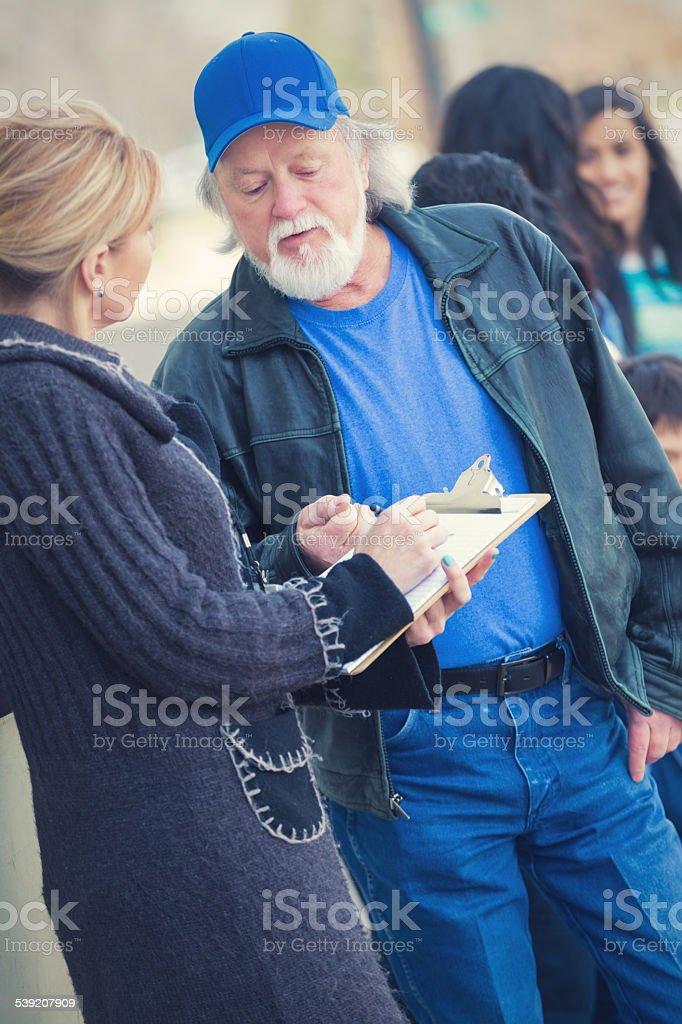 Community volunteer assisting homeless people outside food bank stock photo