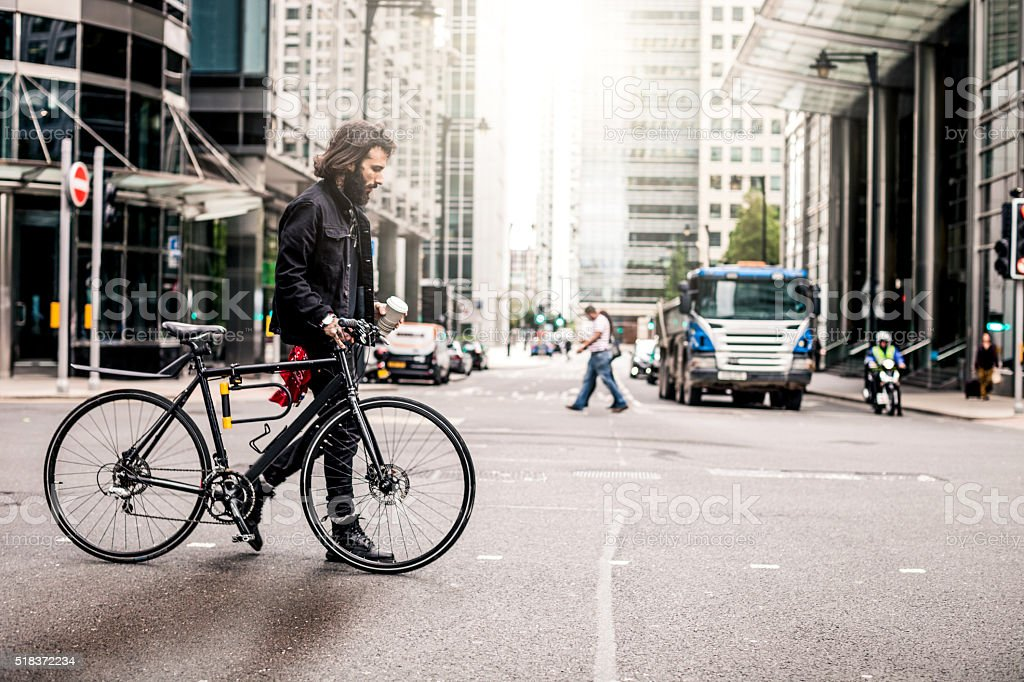 Commuter crossing the road in financial district stock photo