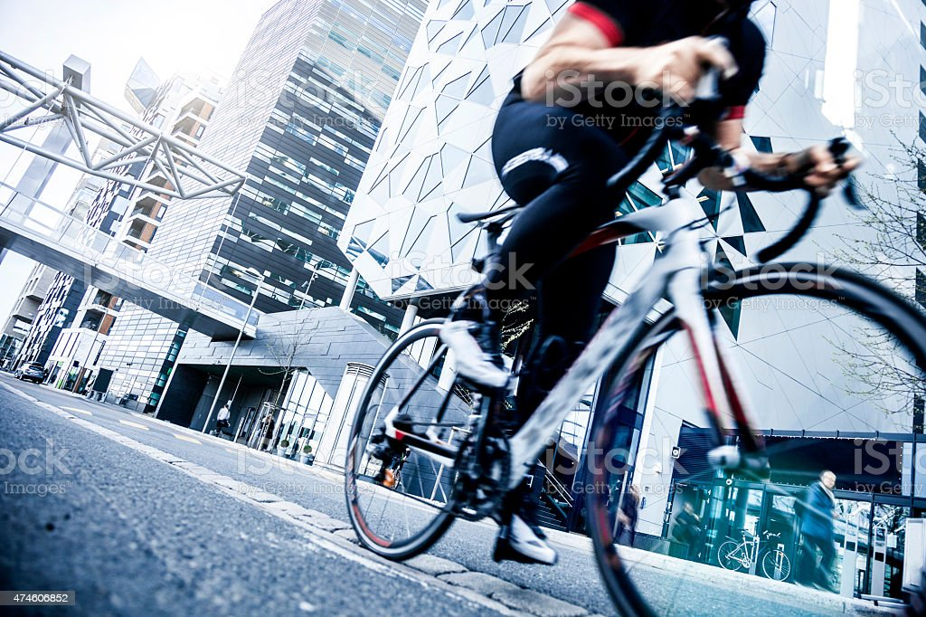 Commuter cycling fast at work in the morning stock photo