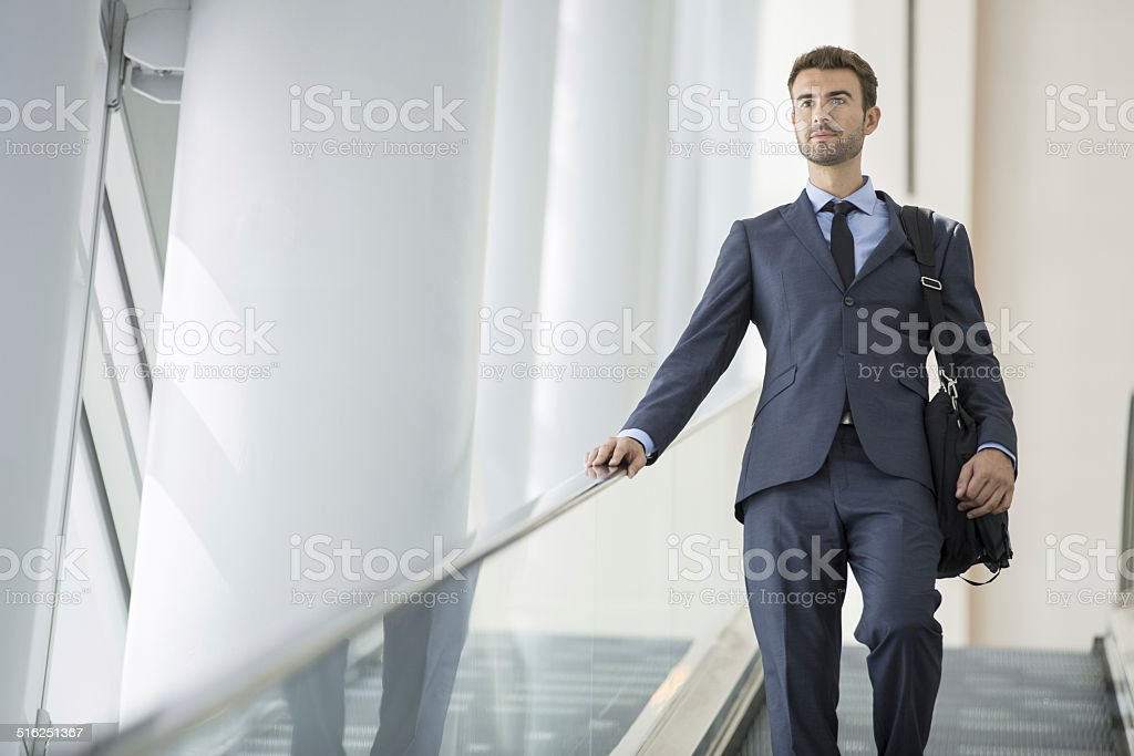 Commuter in the metro station going down the escalator stock photo