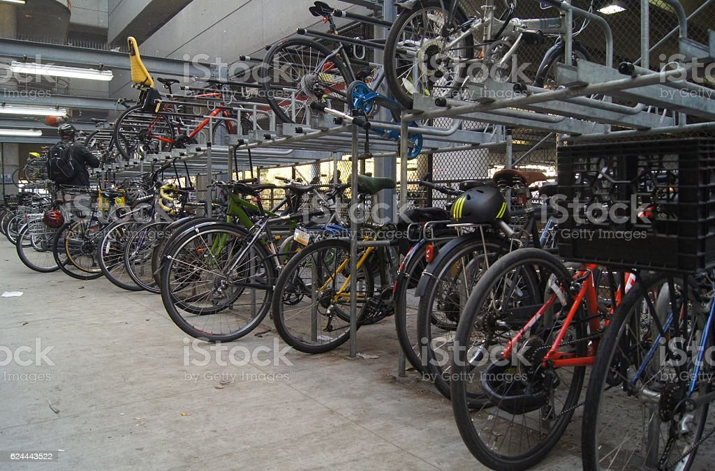 Commuter Parks Bicycle onto Train Station Storage Rack stock photo
