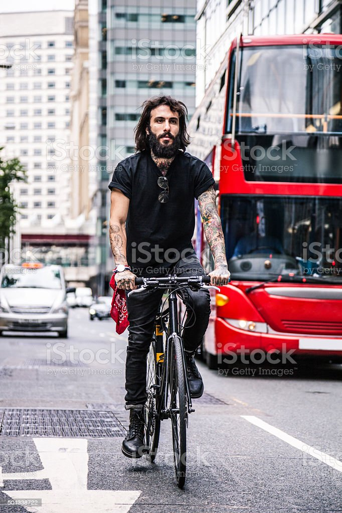 Commuter riding bicycle in financial district stock photo