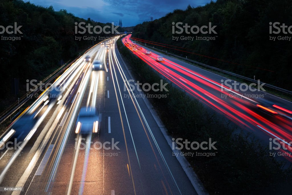 Commuter traffic on highway leaving Cologne City at night stock photo