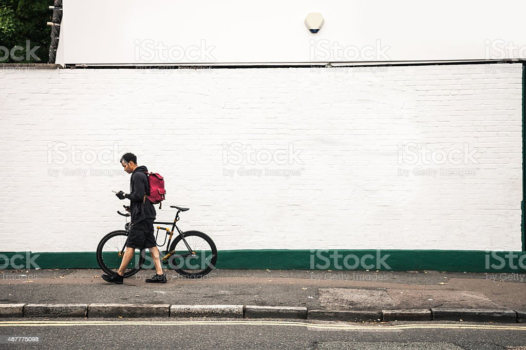 Commuter walking with bicycle in London streets stock photo