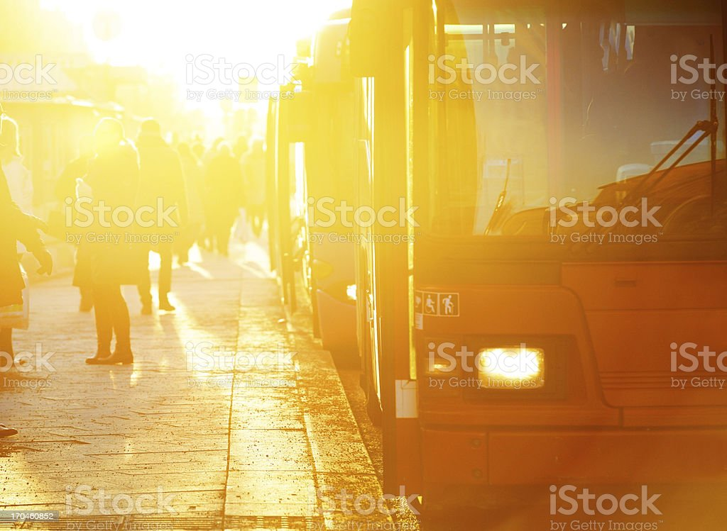 Commuters and red bus in sunset stock photo