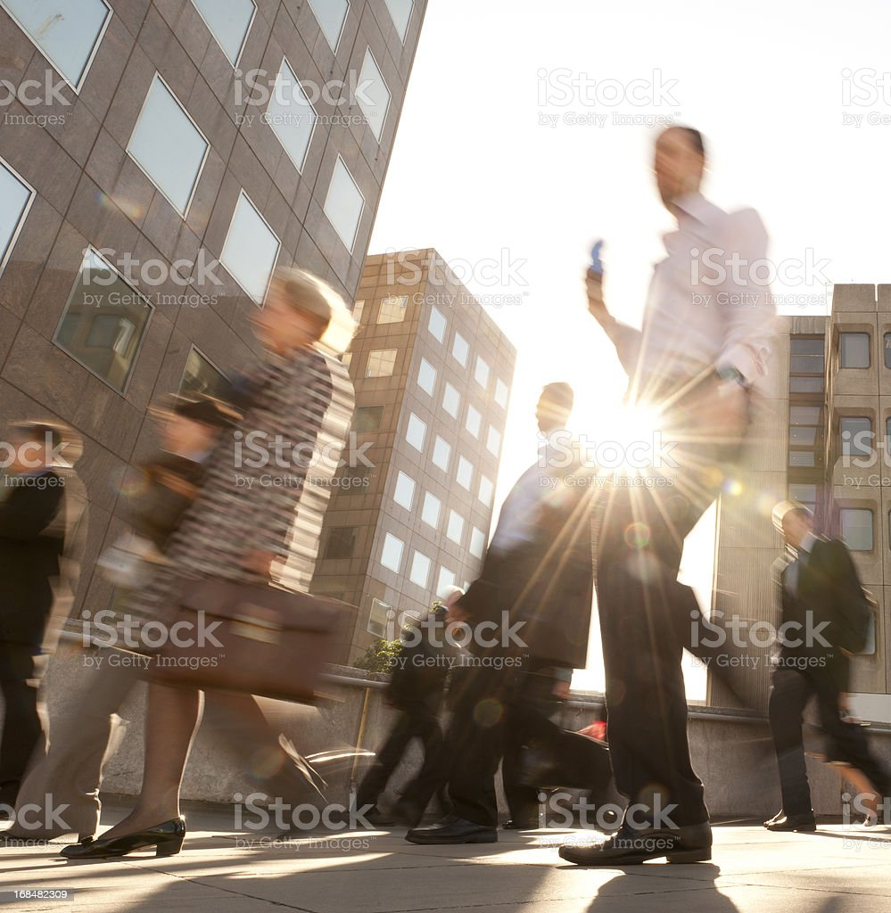 Commuters Backlit by Early Morning Sun stock photo
