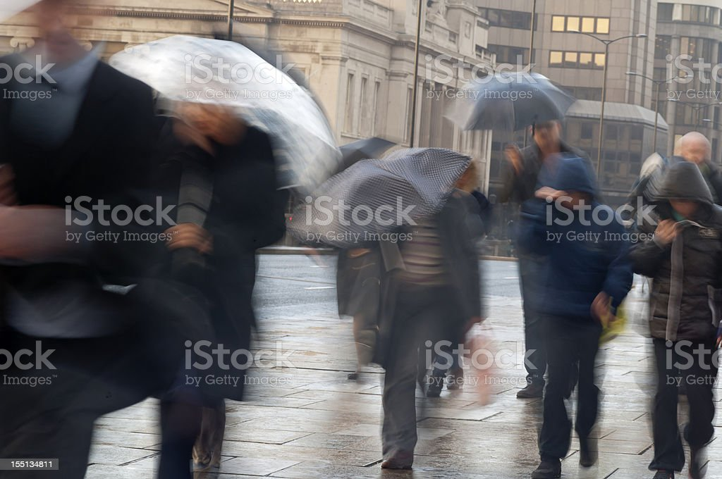 Commuters in the rain with umbrellas with movement blur stock photo