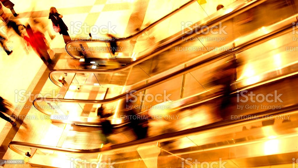 Commuters on an escalator during rush hour stock photo