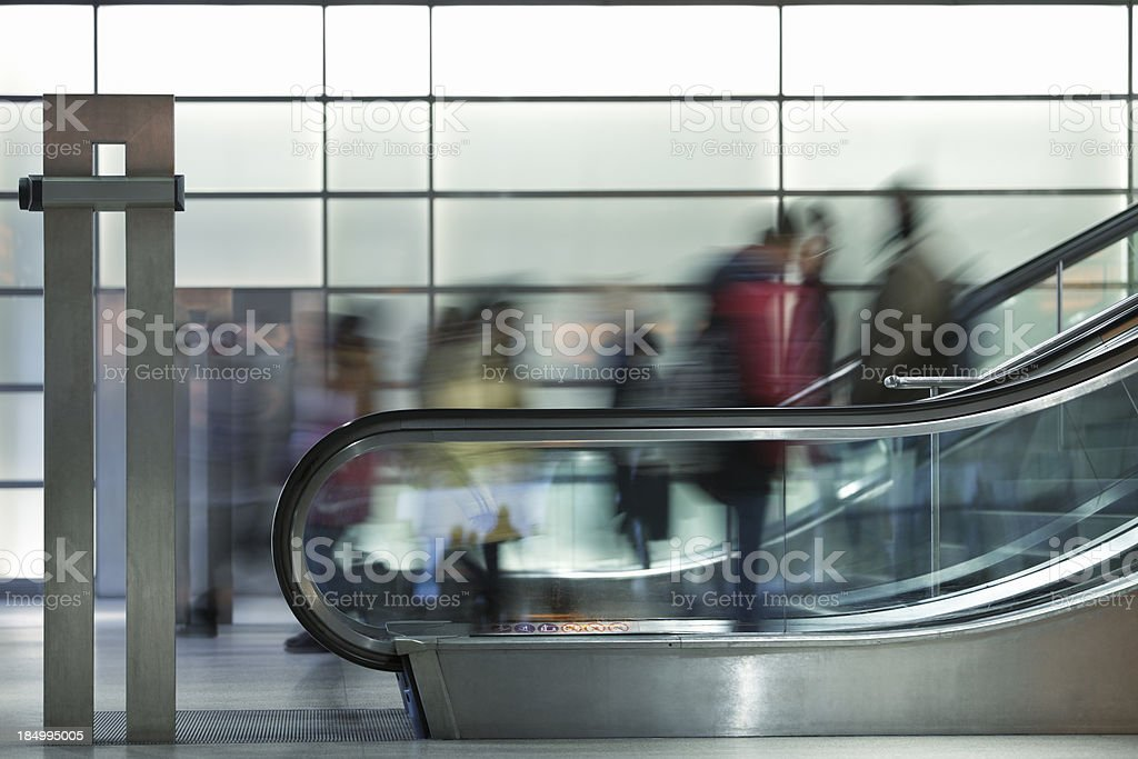 Commuters on Esclalators Against Illuminated Glass Wall, Blurred Motion royalty-free stock photo