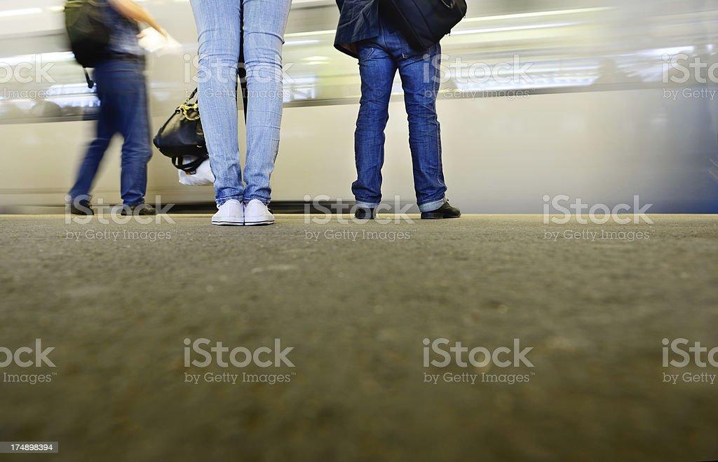 Commuters waiting at subway train station platform royalty-free stock photo