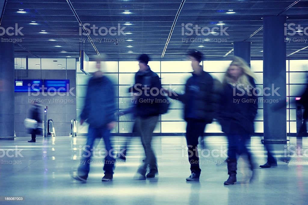 Commuters Walking in Modern Glass Interior, Blurred Motion royalty-free stock photo
