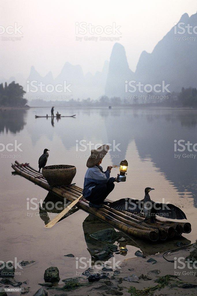 Comorant Birds Sitting on Fisherman's Boat in Li River stock photo