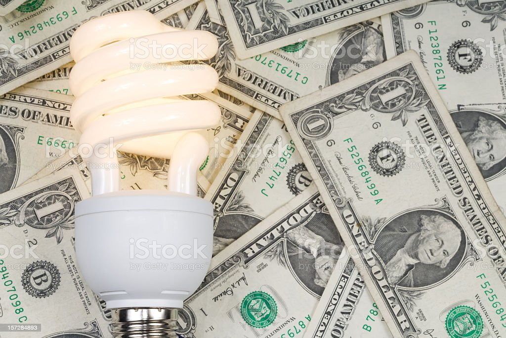 Compact Fluorescent Bulb against Dollar Background stock photo