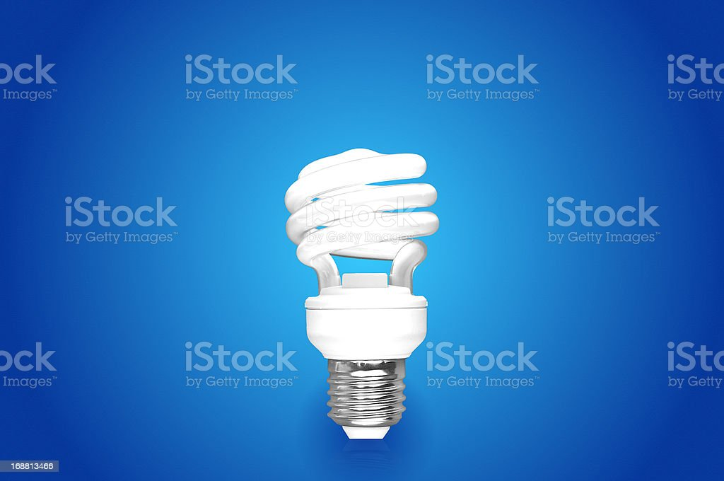 compact fluorescent light bulb on blue background stock photo