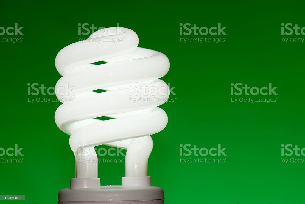 Compact fluorescent lightbulb (CFL) against a green background royalty-free stock photo