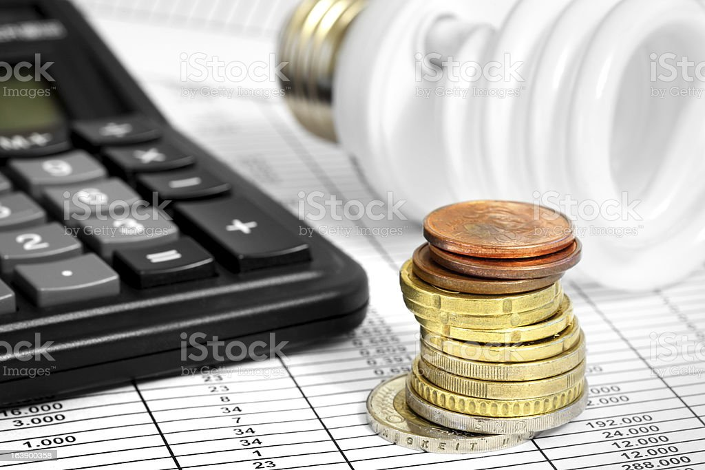 Compact Fluorescent Lightbulb, calculator and coin stack royalty-free stock photo
