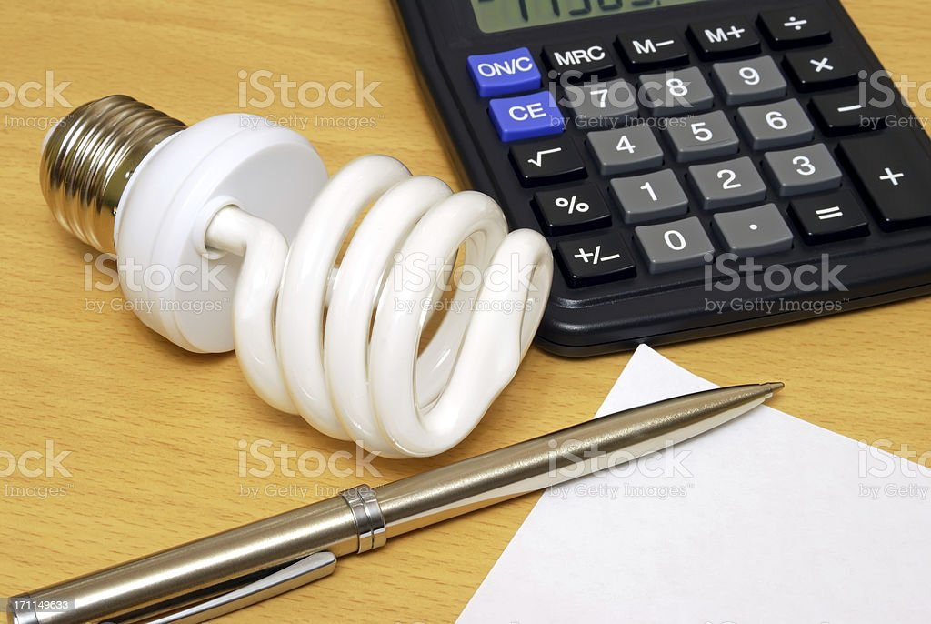 Compact Fluorescent Lightbulb, calculator and pen royalty-free stock photo
