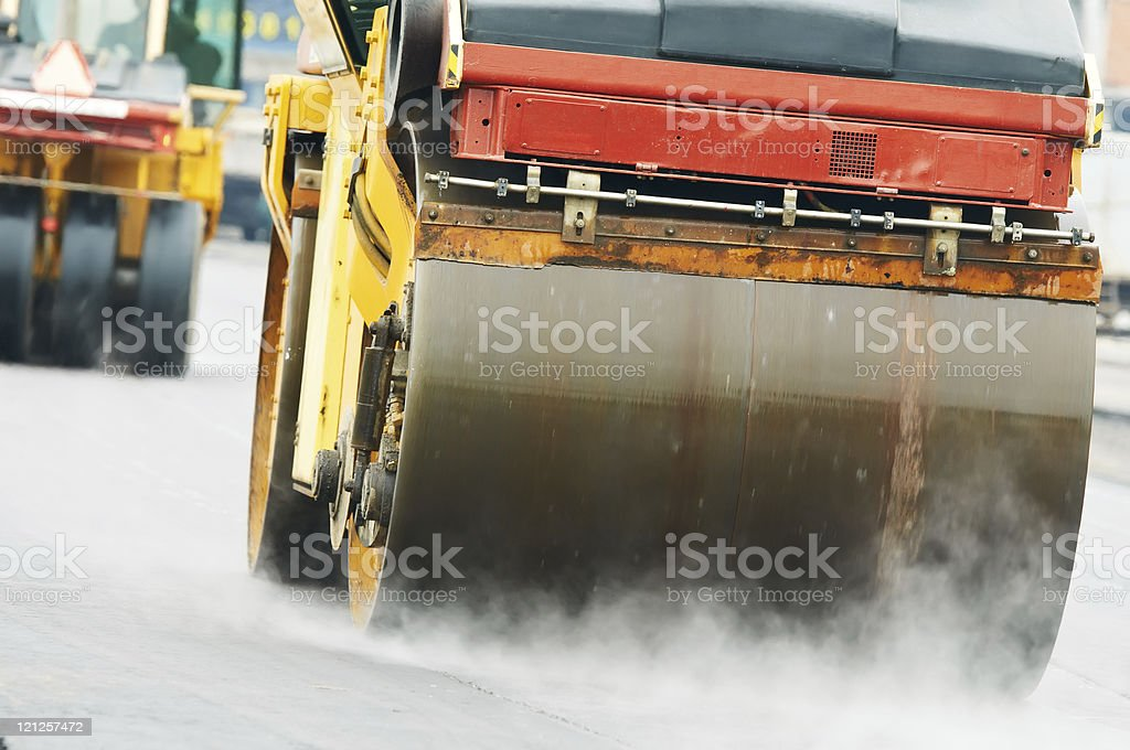 A compactor roller in motion doing asphalt work stock photo