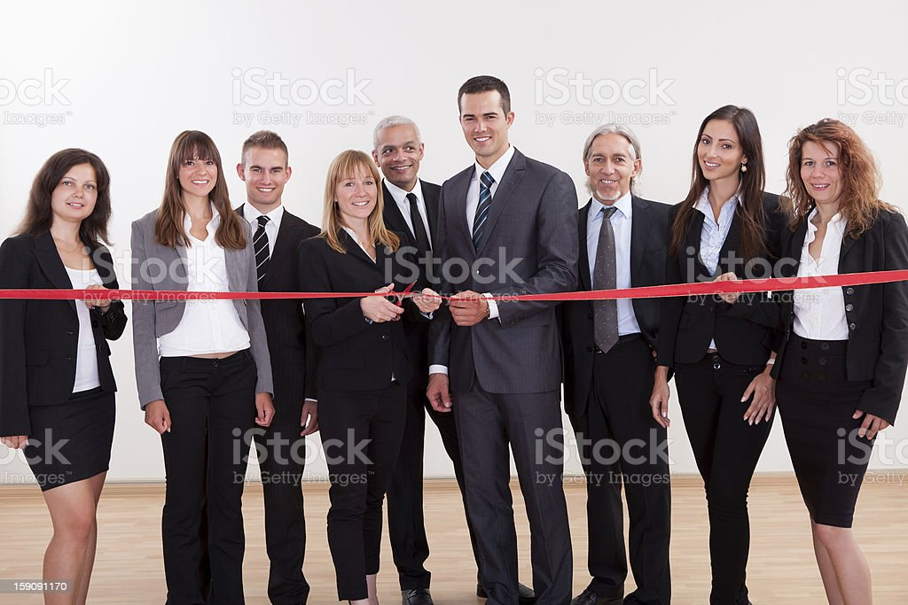 Company management cutting the red ribbon to grand opening stock photo
