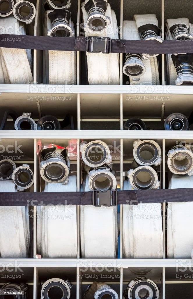 compartment of rolled up fire hoses on a fire truck stock photo