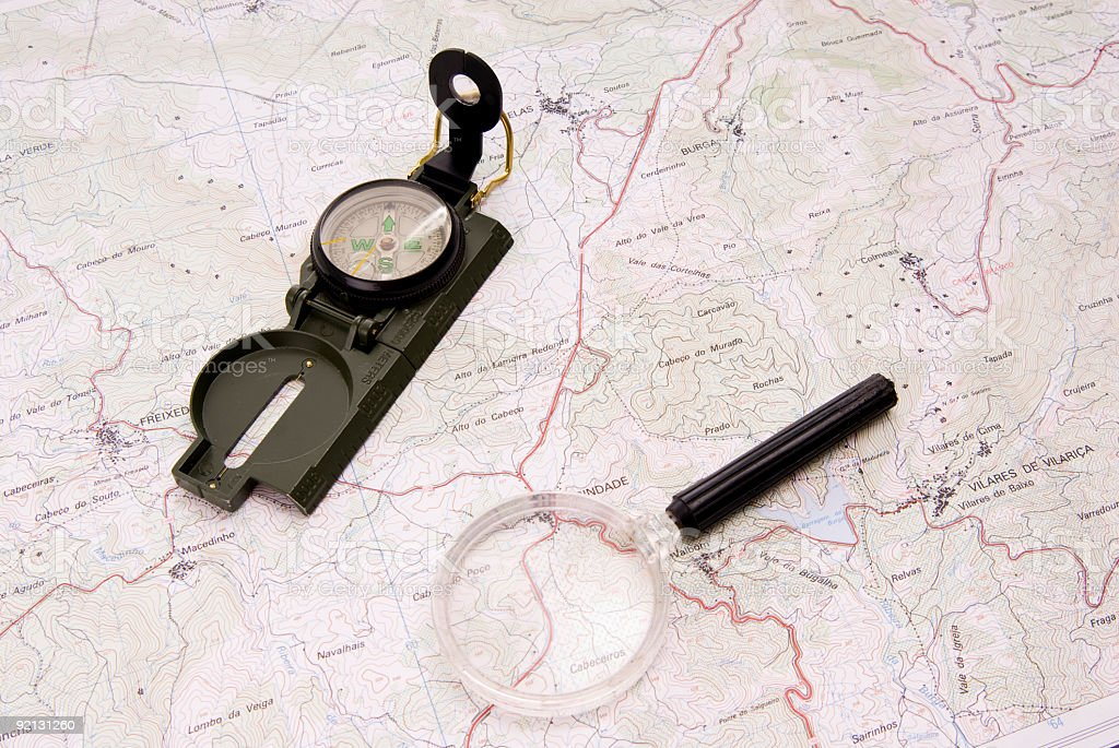 compass and handglass lying on a map royalty-free stock photo