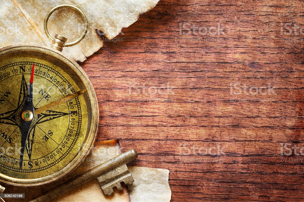 Compass And Key On Wood Surface stock photo