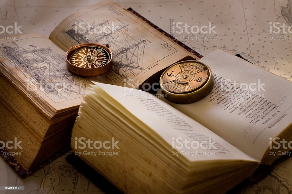 Compass and old books on navigation chart stock photo