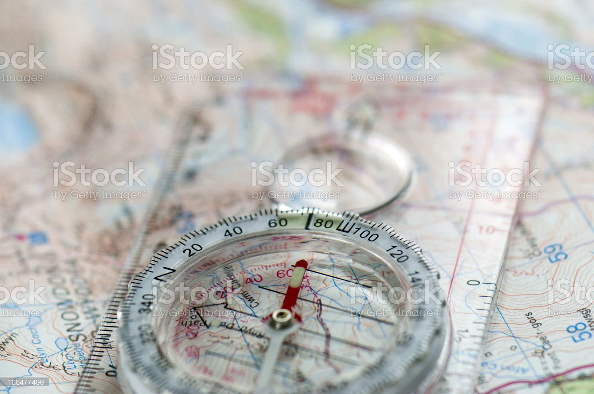 Compass attached to clear ruler sitting on top of a map royalty-free stock photo
