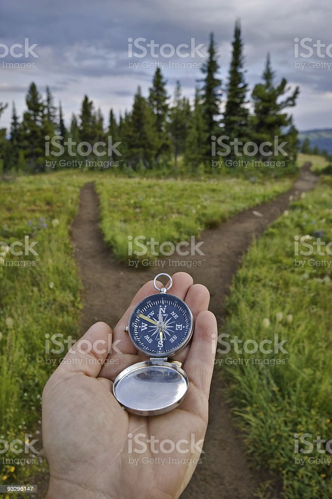 Compass being held out to determine direction stock photo
