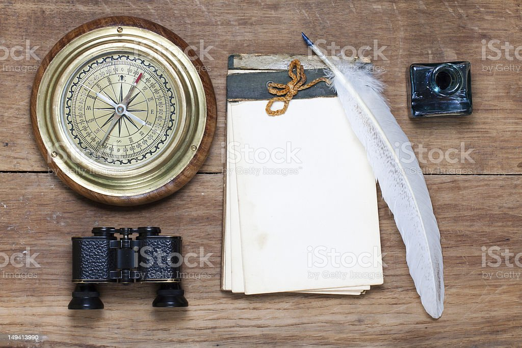 Compass, binoculars, notebook, quill and inkwell on wood royalty-free stock photo