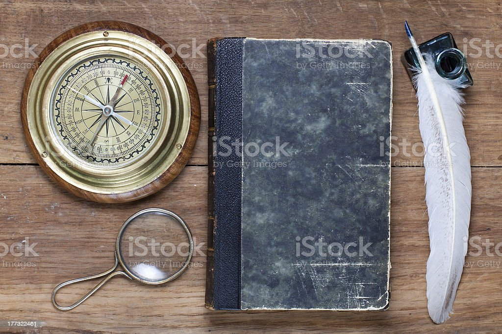 Compass, book, magnifying glass, quill and inkwell on wood royalty-free stock photo