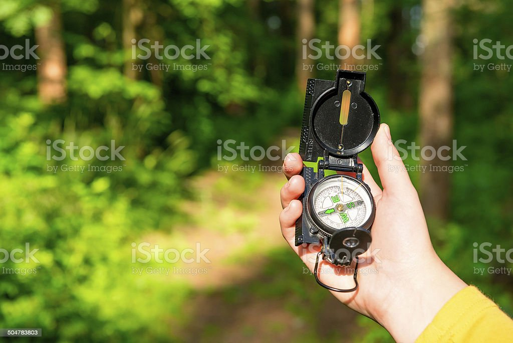 compass in a female hand lost in the woods stock photo