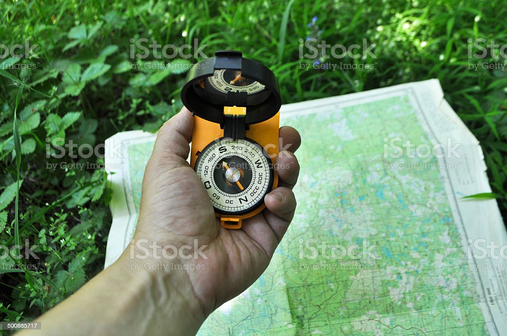 Compass in hand, against background of the map. stock photo