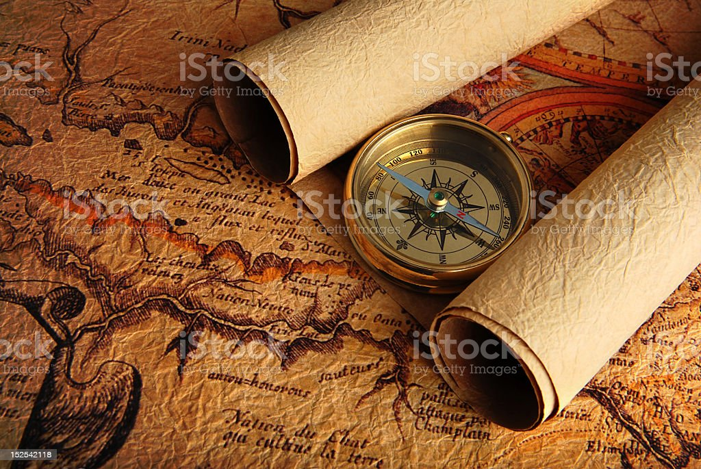 Compass lying on a very old, vintage map royalty-free stock photo