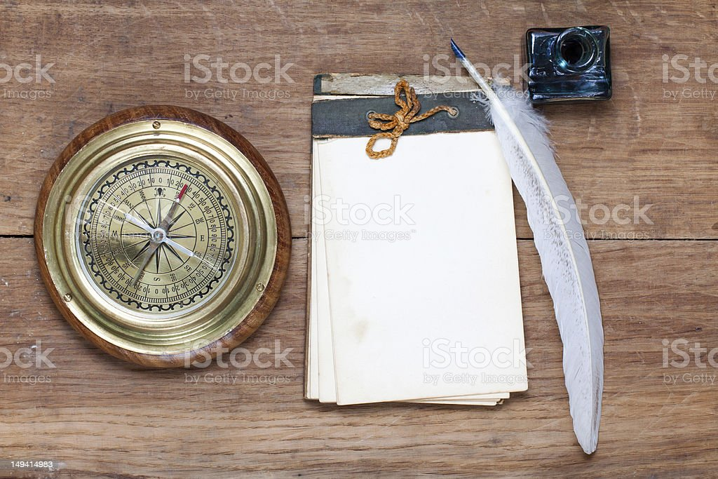 Compass, notepad, quill on wood royalty-free stock photo