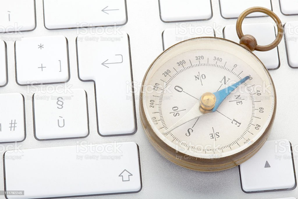 Compass on computer keyboard royalty-free stock photo