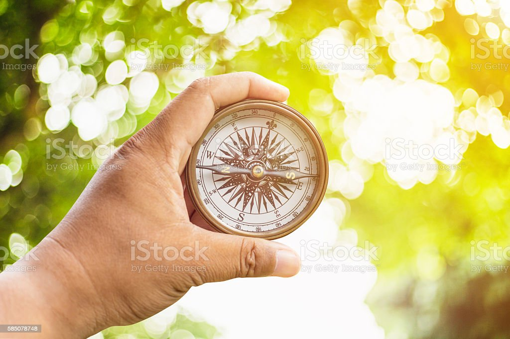 Compass on hand and green bokeh with sunlight. stock photo